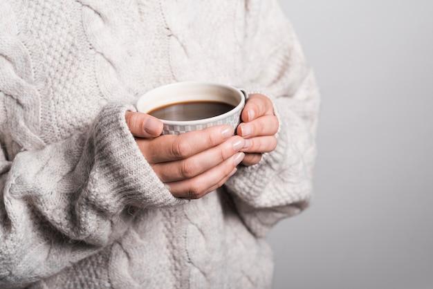 Mittlerer abschnitt der frau in der woolen kleidung, die kaffeetasse hält Kostenlose Fotos