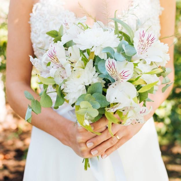 Mittlerer abschnitt der hände einer braut, die schönen blumenblumenstrauß halten Kostenlose Fotos