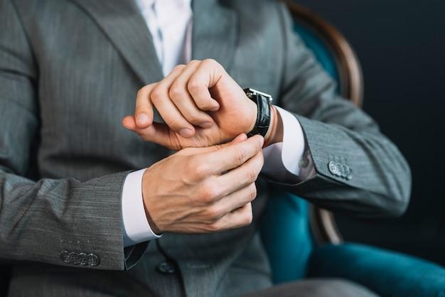Mittlerer abschnitt der hand eines geschäftsmannes, welche die zeit auf armbanduhr aufpasst Kostenlose Fotos