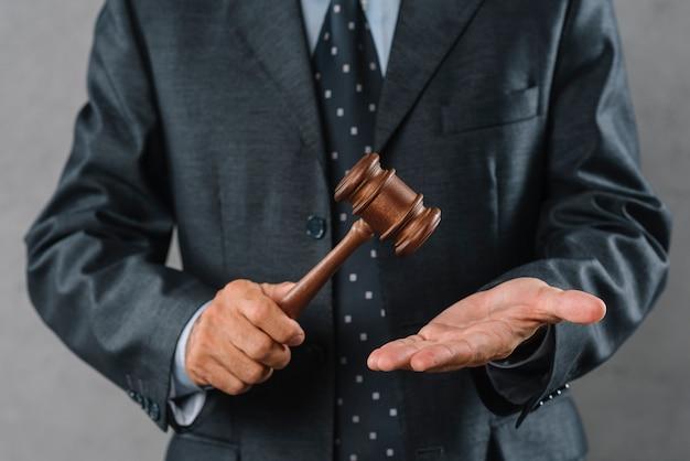 Mittlerer abschnitt des männlichen rechtsanwalts hölzernen holzhammer in der hand halten Kostenlose Fotos