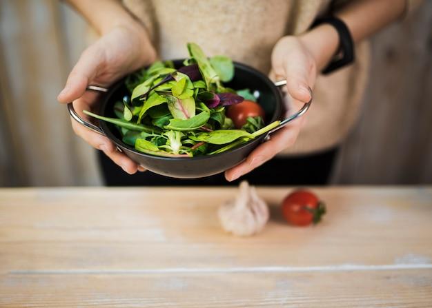 Mittlerer abschnitt einer frau, die frischen belaubten gemüsesalat im behälter über holztisch mit knoblauch und tomate hält Kostenlose Fotos