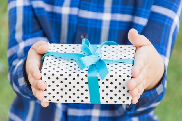 Mittlerer abschnitt einer person, die geschenkbox in der hand gebunden mit blauem band hält Kostenlose Fotos