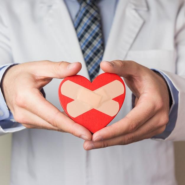 Mittlerer abschnitt eines männlichen doktors, der rotes herz mit gekreuztem verband zeigt Kostenlose Fotos