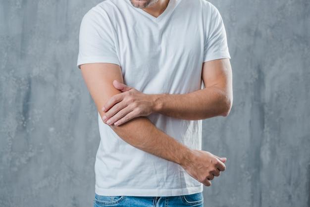 Mittlerer abschnitt eines mannes, der die ellbogenschmerz stehen gegen grauen hintergrund hat Kostenlose Fotos