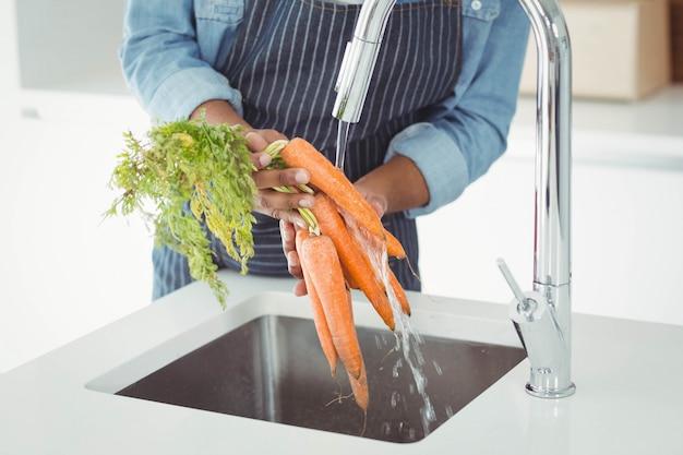 Mittlerer abschnitt von waschenden karotten des mannes in der küche Premium Fotos