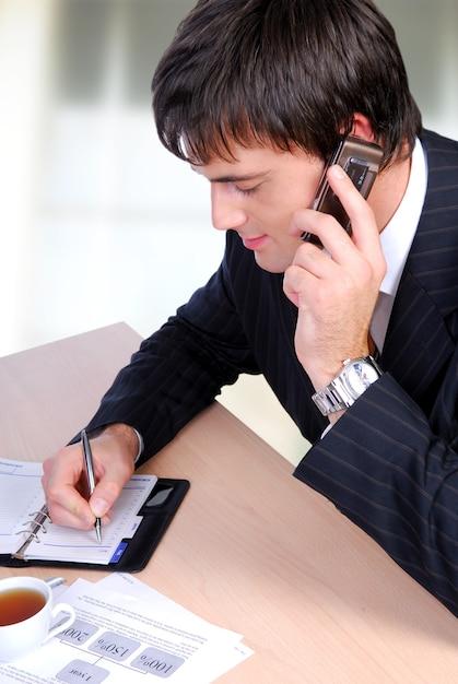 Mittlerer erwachsener mann, der an einem telefon spricht und in organisator schreibt. Kostenlose Fotos