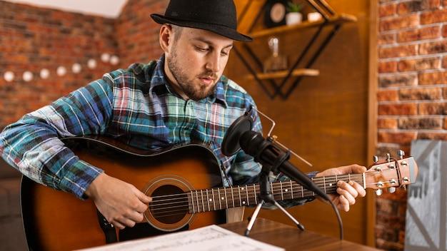 Mittlerer mann mit gitarre und mikrofon Kostenlose Fotos