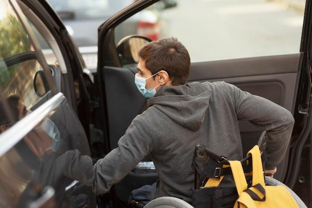 Mittlerer schuss behinderter mann, der maske trägt Kostenlose Fotos