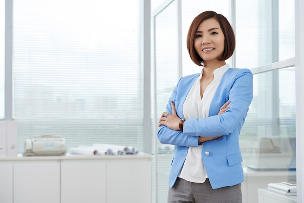Mittlerer schuss der asiatischen geschäftsfrau stehend im büro mit den armen gefaltet Kostenlose Fotos