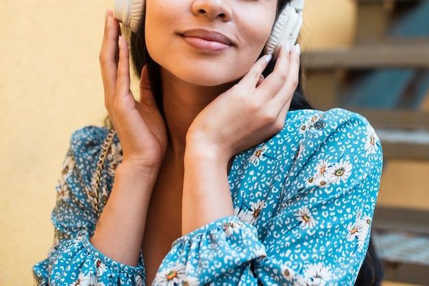 Mittlerer schuss der frau hörend musik Kostenlose Fotos