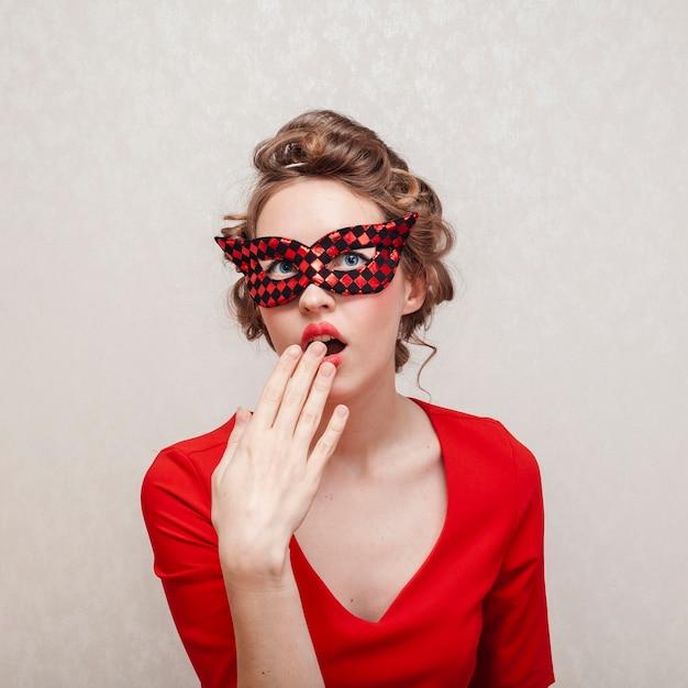 Mittlerer schuss der frau ihr gesicht mit karnevalsmaske bedeckend Kostenlose Fotos