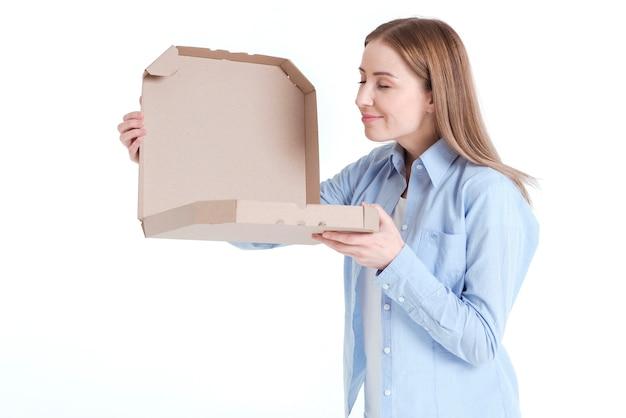 Mittlerer schuss der frau untersuchend einen pizzakasten und -gerüche Kostenlose Fotos
