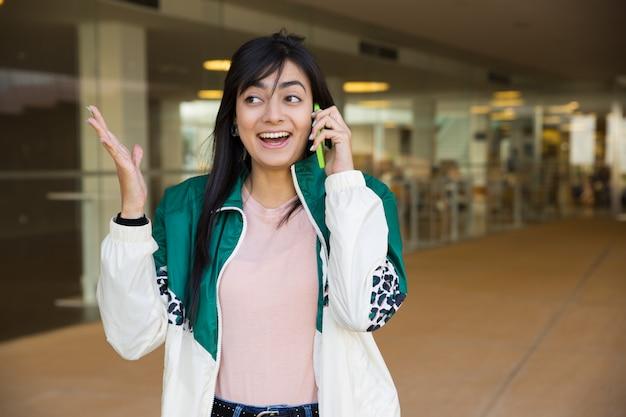 Mittlerer schuss der hübschen frau sprechend am telefon, schauend überrascht Kostenlose Fotos