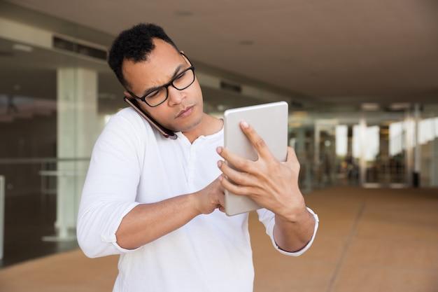 Mittlerer schuss des ernsten mannes arbeitend an der tablette, sprechend am telefon Kostenlose Fotos