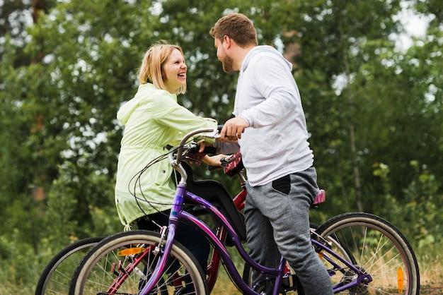 Mittlerer schuss des glücklichen paars auf fahrrädern Kostenlose Fotos