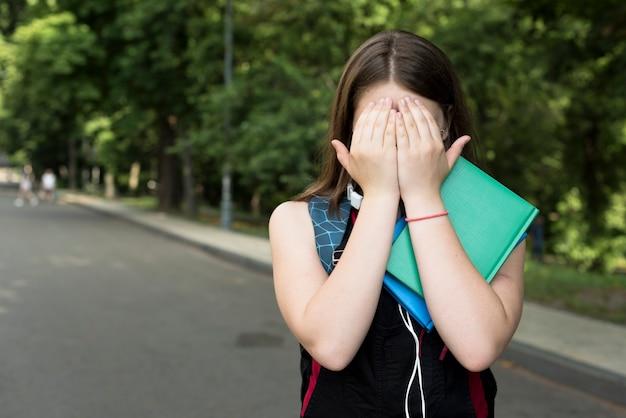 Mittlerer schuss des highschool mädchens ihr gesicht mit den händen bedeckend Kostenlose Fotos
