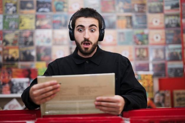 Mittlerer schuss des jungen mannes hörend musik im vinylspeicher Kostenlose Fotos