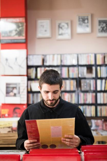 Mittlerer schuss des jungen mannes vinyls im speicher suchend Kostenlose Fotos