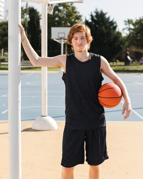 Mittlerer schuss des jungen mit basketballball Kostenlose Fotos