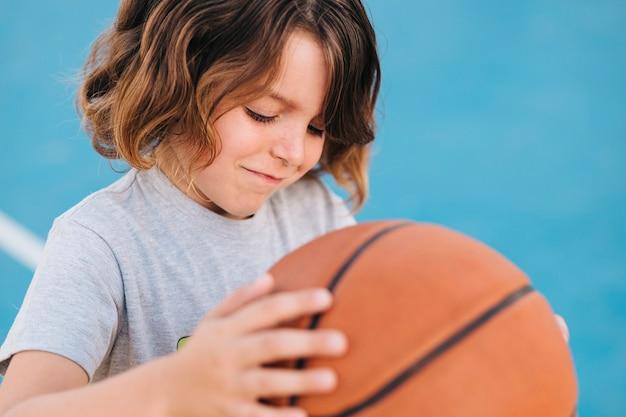 Mittlerer schuss des kindes basketball spielend Kostenlose Fotos