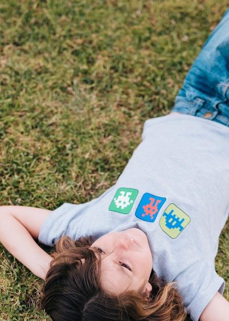 Mittlerer schuss des kindes liegend auf gras Kostenlose Fotos