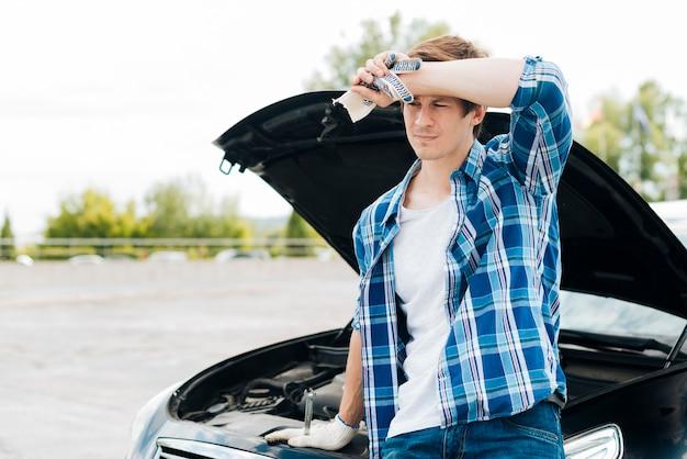 Mittlerer schuss des mannes mit auto im hintergrund Kostenlose Fotos