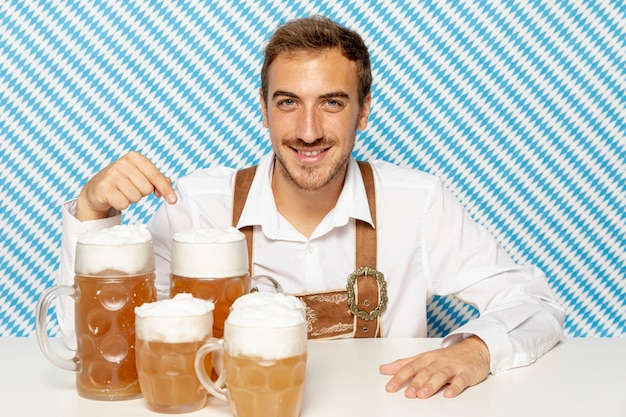 Mittlerer schuss des mannes mit blonden bierpints Kostenlose Fotos