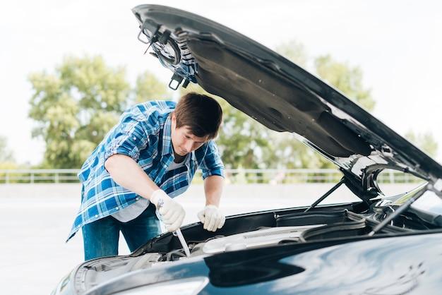 Mittlerer schuss des mannes motor reparierend Kostenlose Fotos