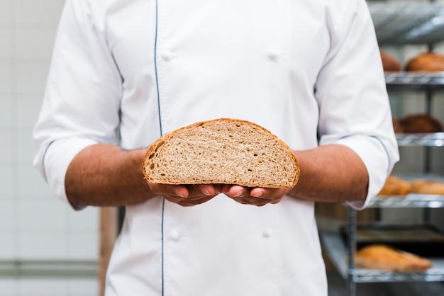 Mittlerer schuss eines bäckers, der in der hand halbiertes brot hält Kostenlose Fotos