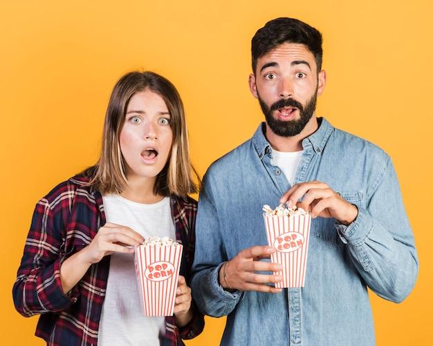 Mittlerer schuss entsetzte paare mit popcorn Kostenlose Fotos