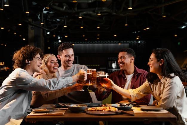 Mittlerer schuss glückliche freunde mit bierkrügen Kostenlose Fotos