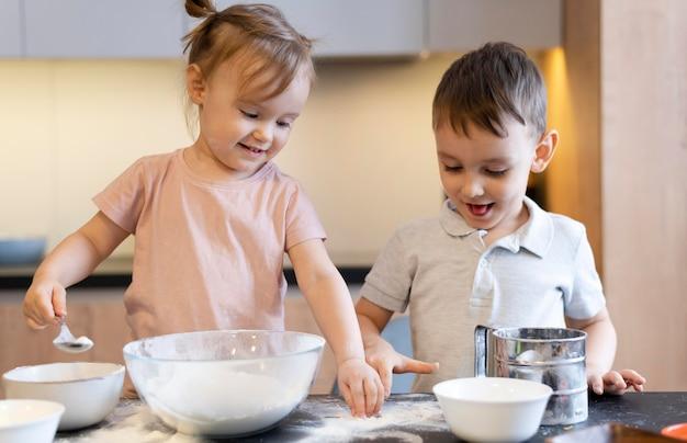 Mittlerer schuss glückliche kinder in der küche Kostenlose Fotos