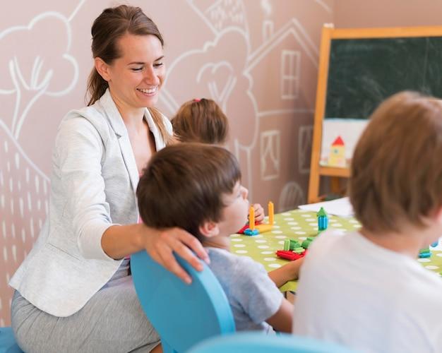 Mittlerer schuss glücklicher lehrer mit kindern Kostenlose Fotos