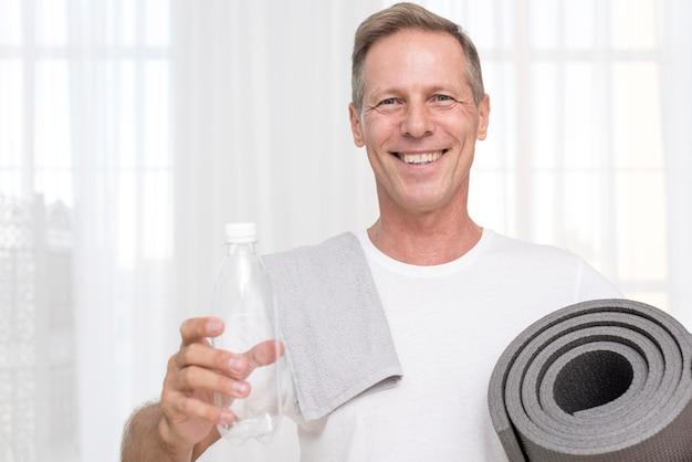 Mittlerer schuss glücklicher mann mit yogamatte und -tuch Kostenlose Fotos