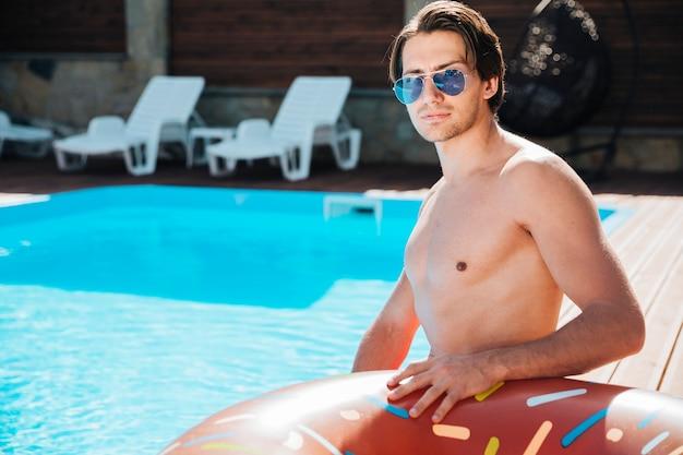 Mittlerer schuss junger mann am pool Kostenlose Fotos