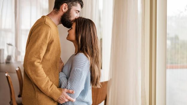 Mittlerer schuss mann, der frau auf stirn küsst Premium Fotos
