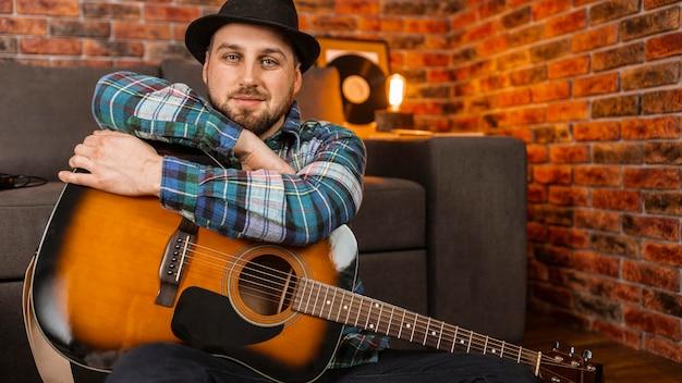 Mittlerer schuss mann, der gitarre hält Kostenlose Fotos