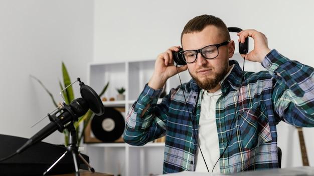 Mittlerer schuss mann, der kopfhörer hält Kostenlose Fotos