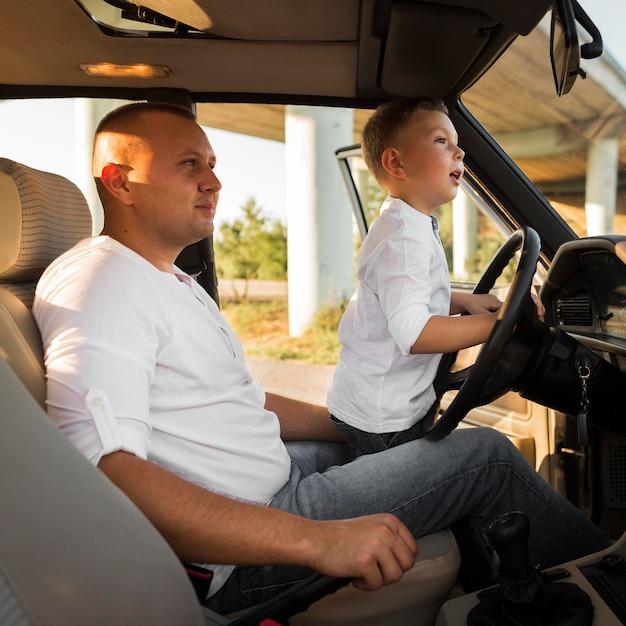 Mittlerer schuss mann und kind im auto Premium Fotos