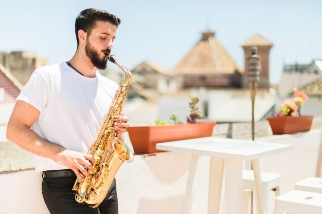 Mittlerer schuss seitlich mann, der das saxophon spielt Kostenlose Fotos