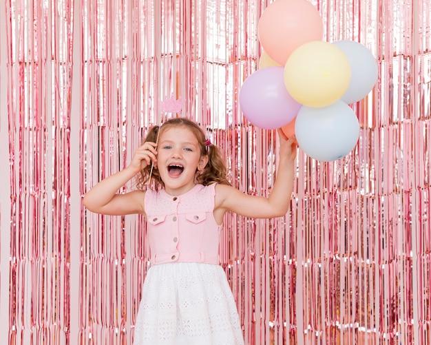 Mittlerer schuss smiley-mädchen, das luftballons hält Kostenlose Fotos