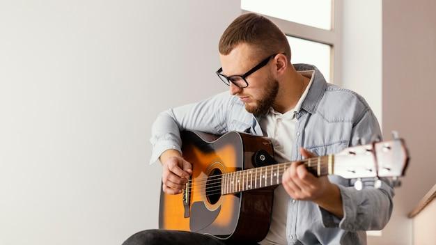 Mittlerer schuss smiley-mann, der drinnen gitarre spielt Kostenlose Fotos