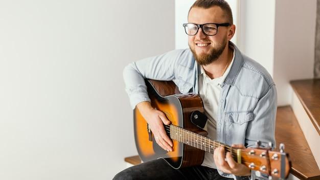 Mittlerer schuss smiley-mann, der gitarre spielt Kostenlose Fotos