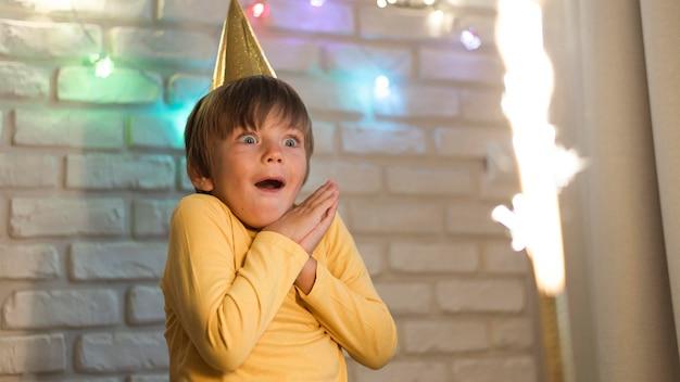 Mittlerer schuss überraschte kind, das feuerwerk beobachtet Kostenlose Fotos