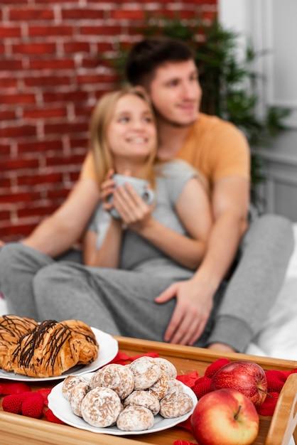 Mittlerer schuss verwischte paare mit frühstück im bett Kostenlose Fotos