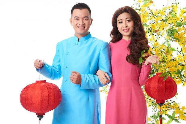 Mittlerer schuss von asiatischen paaren in den traditionellen ausstattungen, die rote laternen halten Kostenlose Fotos