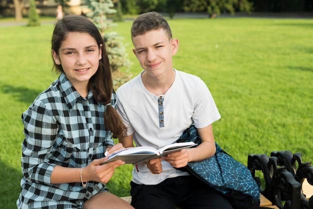 Mittlerer schuss von den highschool freunden, die ein buch auf bank teilen Kostenlose Fotos