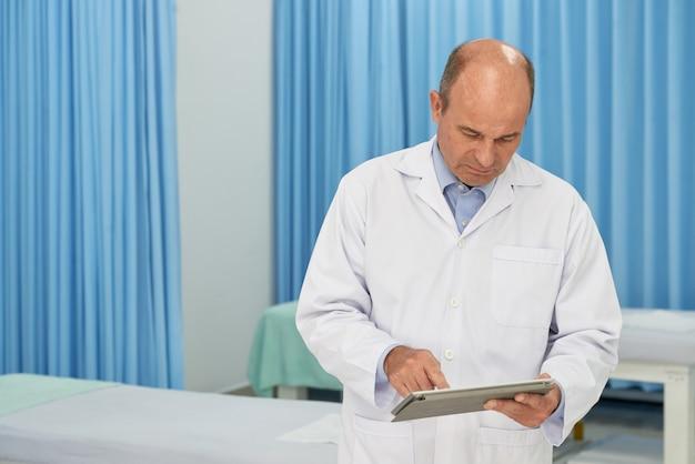 Mittlerer schuss von doktor krankengeschichte auf digitalem auflagengerät überprüfend Kostenlose Fotos