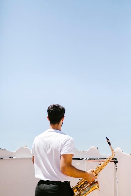 Mittlerer schuss zurück sehen den musiker an, der saxophon hält Kostenlose Fotos