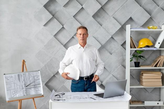 Mittlerer schussarchitekt, der in seinem büro aufwirft Kostenlose Fotos
